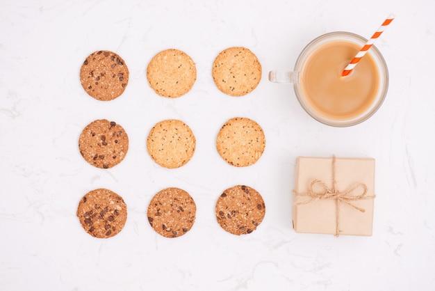 Kopje koffie onder patroon van verschillende zandkoekjes en haverkoekjes met granen en rozijnen op zwarte houten achtergrond. bovenaanzicht, plat gelegd.
