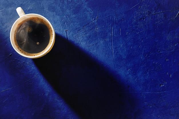 Kopje koffie op blauwe achtergrond, bovenaanzicht