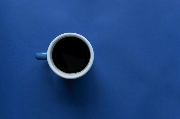 Kopje koffie op blauwe tafel, bovenaanzicht