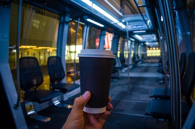 Kopje koffie op de luchthaven mans hand met zwarte kop