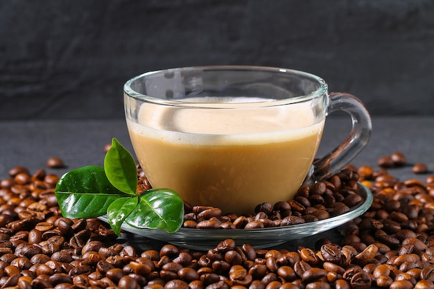 Kopje koffie op een grijze tafel met koffiebonen en koffiebladeren