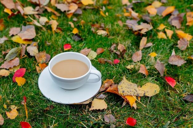 Kopje koffie op een groene weide met bladeren