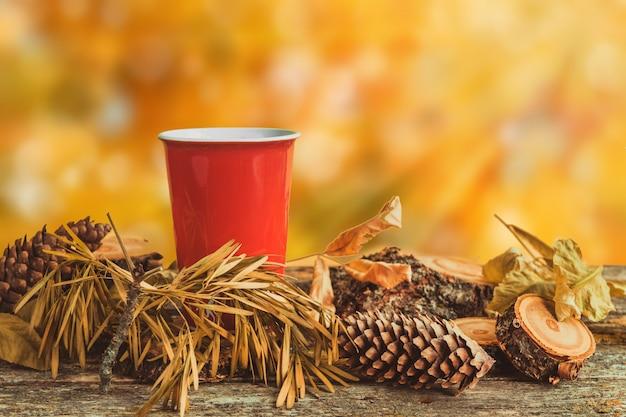 Kopje koffie op een houten tafel tussen de bladeren en kegels