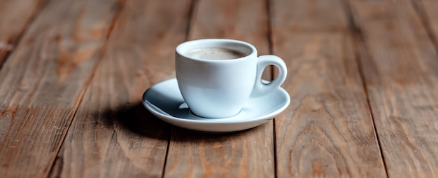 Kopje koffie op een oude houten tafel. wit keramiek. aromatische koffie met schuim