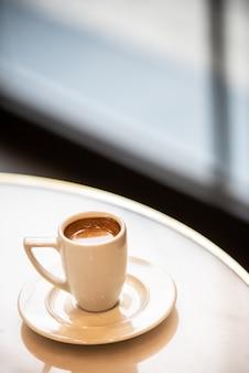 Kopje koffie op een ronde tafel, verticaal.
