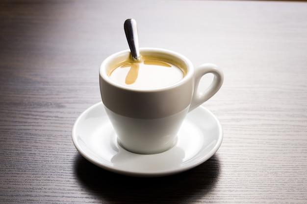 Kopje koffie op een schotel met een lepel op tafel