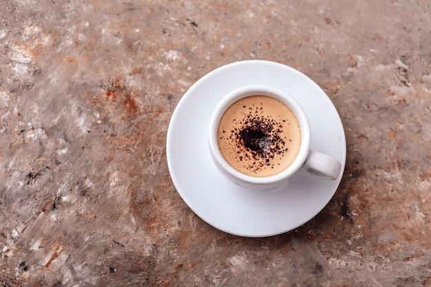 Kopje koffie op grijze achtergrond enkele kop koffie met room en chocoladeschilfers