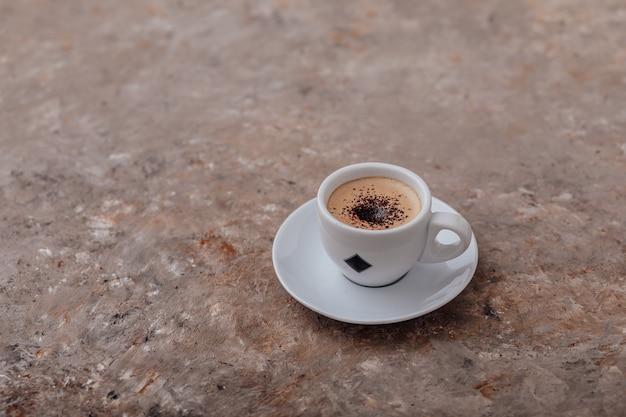 Kopje koffie op grijze achtergrond enkele kop koffie met roomchocoladeschilfers grijze achtergrond