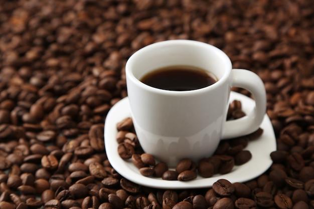 Kopje koffie op koffiebonen achtergrond beans