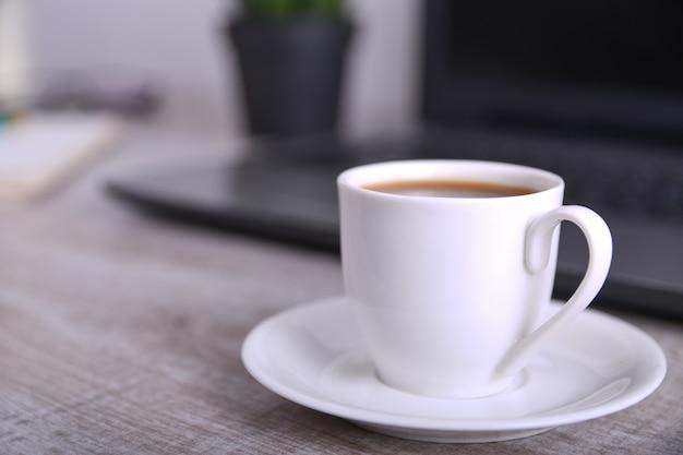 Kopje koffie op office-bureaublad met laptop, computer op houten tafel. detailopname
