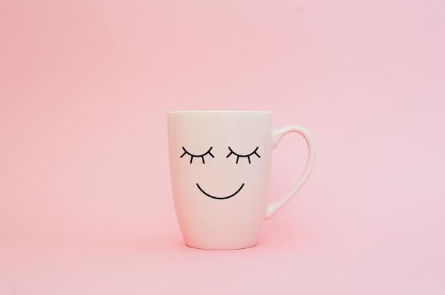 Kopje koffie op roze achtergrond met gelukkige glimlach gezicht
