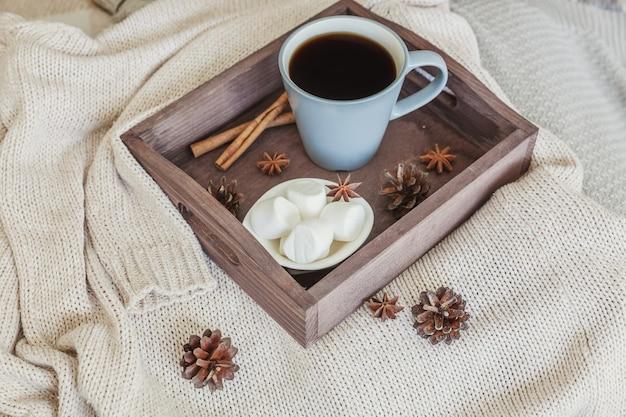 Kopje koffie op rustieke houten dienblad, zoete marshmallow en warme wollen trui
