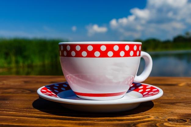 Kopje koffie op rustieke houten tafel aan de rivier