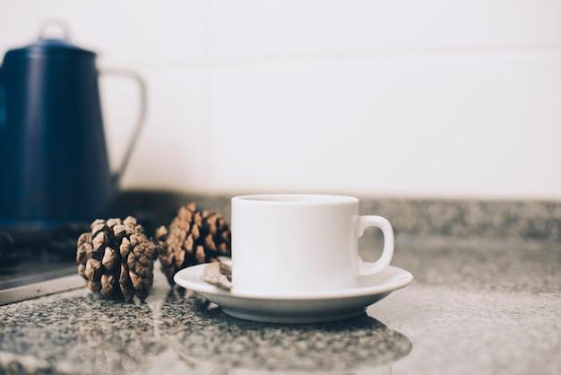Kopje koffie op schotel en pinecone op aanrecht tegen witte achtergrond