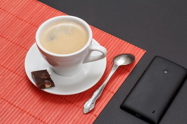 Kopje koffie op schotel met stuk chocoladereep en lepel op bamboe servet, mobiele telefoon op een zwarte achtergrond. bovenaanzicht.