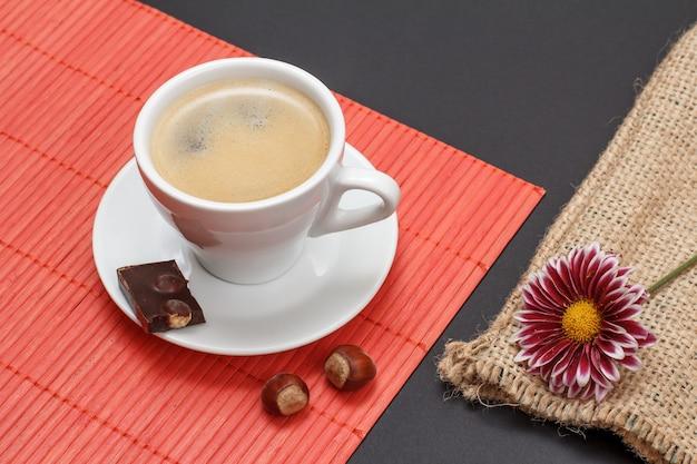 Kopje koffie op schotel met stuk chocoladereep, noten op bamboe servet, zak en bloemknop op een zwarte achtergrond. bovenaanzicht.