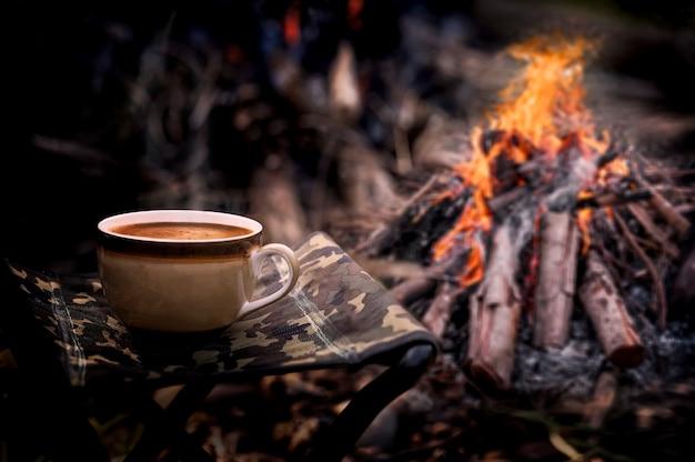 Kopje koffie op veld stoel met vreugdevuur achtergrond.