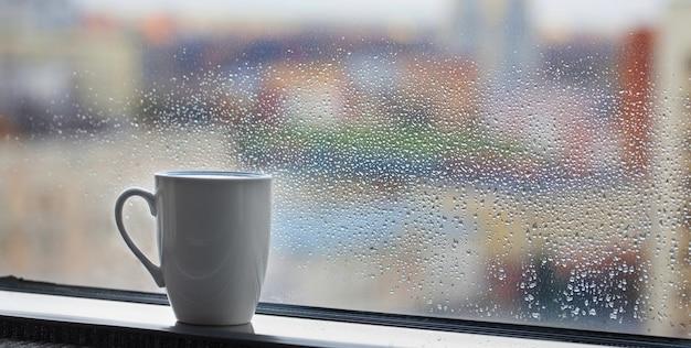 Kopje koffie op vensterbank met regendruppels op glas
