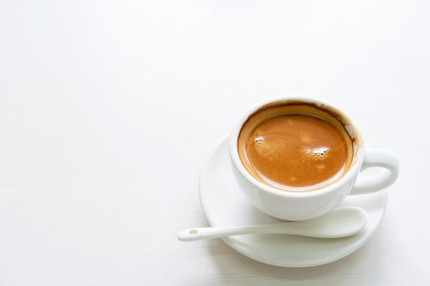 Kopje koffie op witte tafel met copyspace.