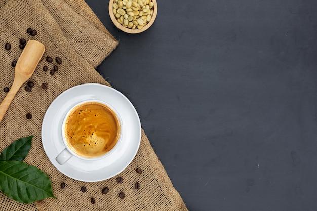 Kopje koffie op zak met bladeren, koffiebonen en kom met pinda's