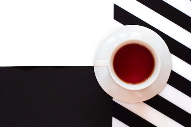 Kopje koffie op zwart-witte tafel met strepen in minimalistische stijl