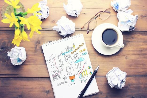 Kopje koffie, pen, notitieblok, papieren, glazen en bloem op houten tafel