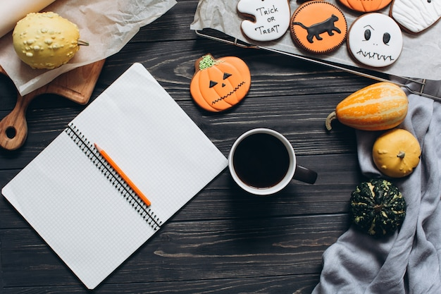 Kopje koffie, peperkoek voor halloween, notitieboekje en pompoenen.