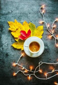 Kopje koffie rode en gele herfstbladeren gloeiende slinger op een betonnen achtergrond