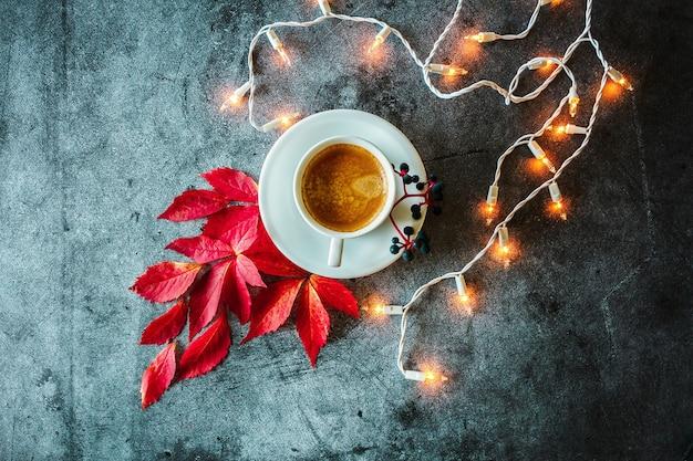 Kopje koffie rode herfstbladeren bessen gloeiende slinger op een betonnen achtergrond