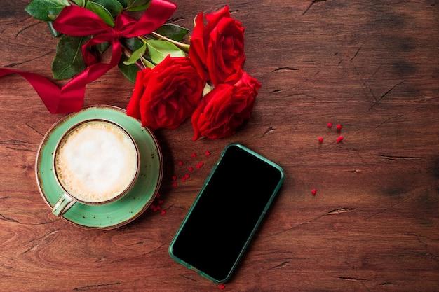 Kopje koffie, rode rozen en een telefoon met vrije ruimte voor inhoud