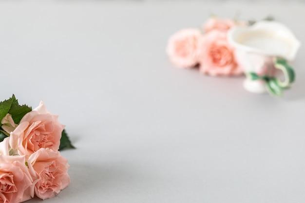 Kopje koffie, roze rozen, roze rozen op een grijs