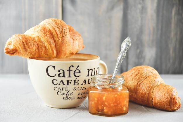 Kopje koffie, twee croissants en appeljam in een glazen pot