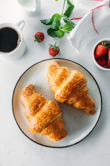 Kopje koffie, vers gebakken croissants en verse aardbeien op houten achtergrond