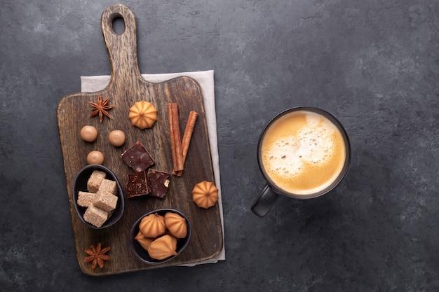 Kopje koffie, verschillende snoepjes en kruiden op steen.