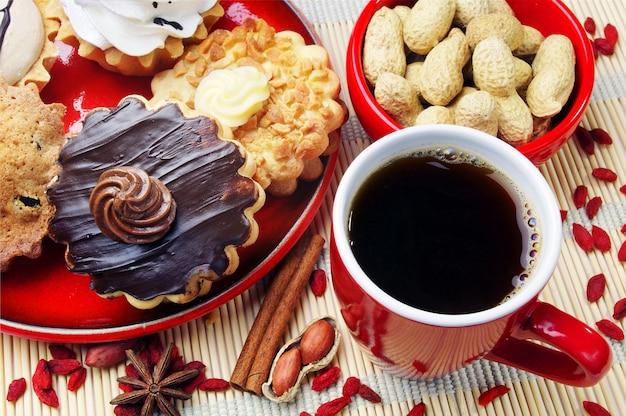 Kopje koffie, verschillende taarten en pinda's close-up