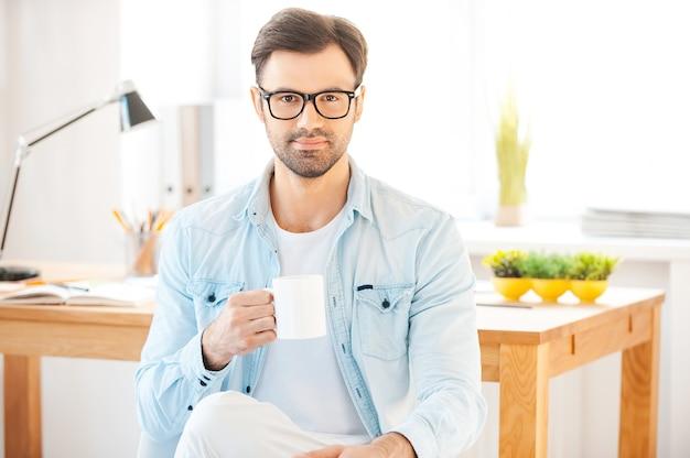 Kopje koffie voor geweldige ideeën. knappe jonge man in shirt en bril die een kopje koffie vasthoudt en naar de camera kijkt terwijl hij voor zijn werkplek zit