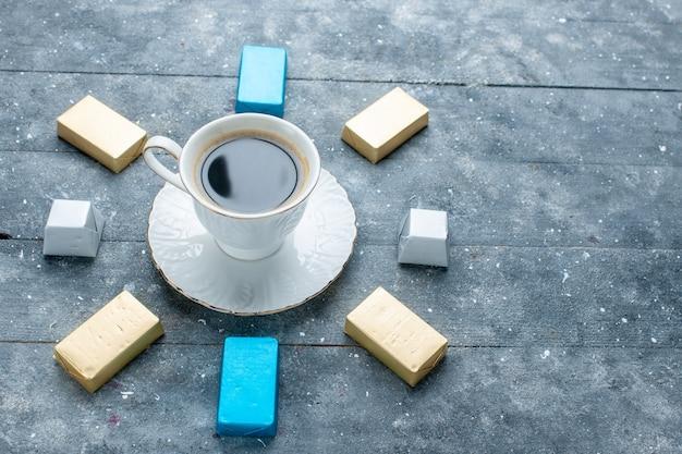 Kopje koffie warm en sterk met beklede goudgevormde chocolade op lichtblauw bureau, koffie cacaodrank