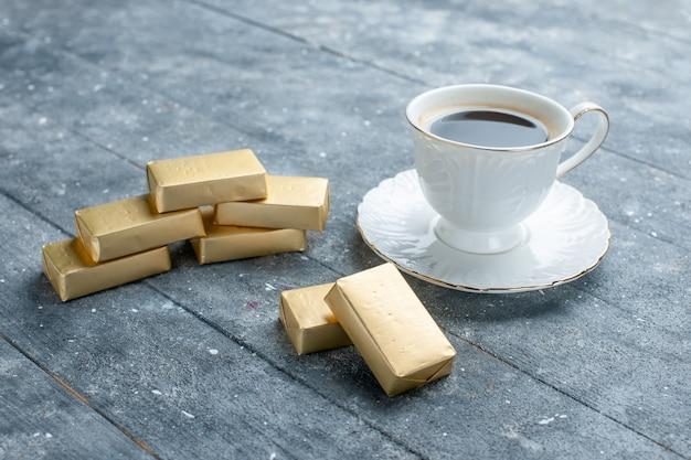 Kopje koffie warm en sterk met goudgevormde chocolade op blauw, koffie cacaodrank heet