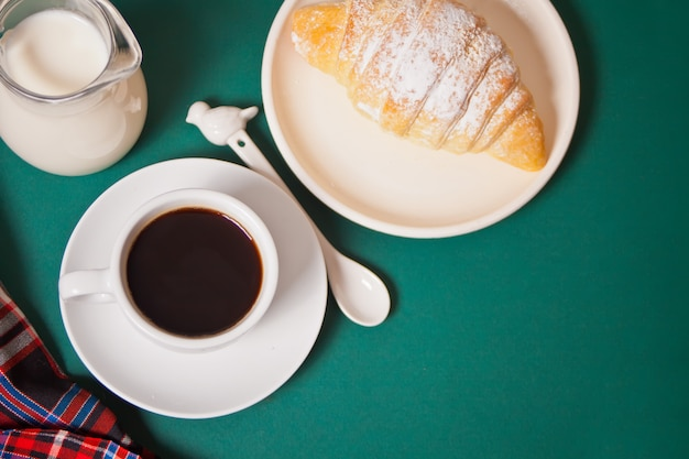 Kopje koffie, zelfgemaakte broodje croissant op groen