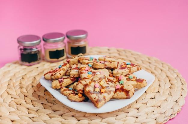Kopje koffie, zelfgemaakte koekjes en keukengerei op een roze achtergrond.