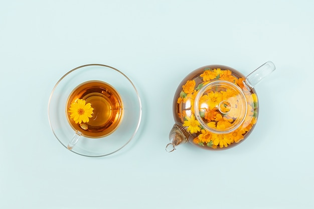 Kopje kruidenthee en transparante theepot met calendula bloemen op blauwe achtergrond. calendula-thee komt ten goede aan uw gezondheidsconcept.