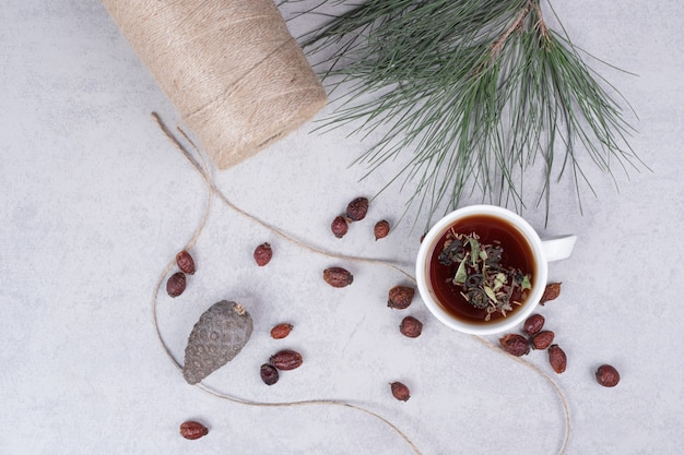 Kopje kruidenthee, gedroogde veenbessen en dennenappel op marmeren tafel. hoge kwaliteit foto