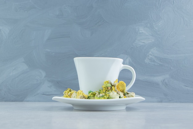 Kopje kruidenthee met gele bloemen.