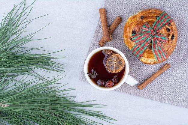 Kopje kruidenthee met rozijnenbroodje op tafelkleed. hoge kwaliteit foto