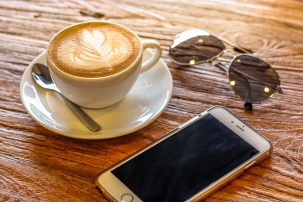 Kopje latte art koffie met lepel en bord op de bruine bast mooi met warm licht versierd met zonnebril en mobiele telefoon