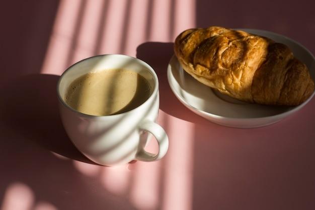 Kopje latte koffie met croissant op pastelroze achtergrond met harde schaduwen van jaloezieën.