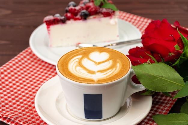 Kopje latte koffie met een stukje bessenkaastaart