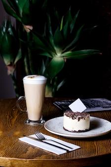 Kopje latte met chocolade bestrooid cheesecake