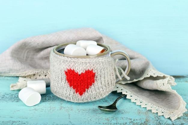 Kopje lekkere warme chocolademelk, op houten tafel, op kleur achtergrond