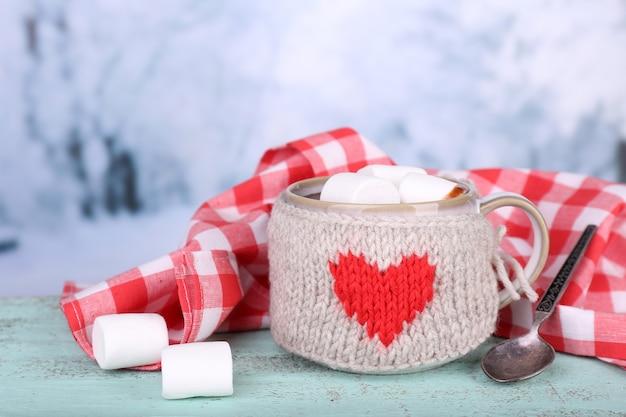 Kopje lekkere warme chocolademelk, op houten tafel, op lichte ondergrond